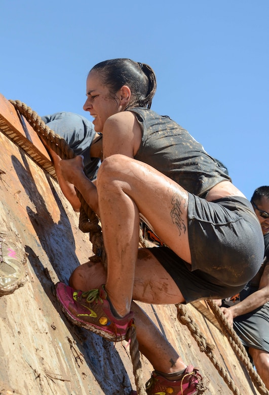Master Sgt. Larita Trudell, 12th Air Force (Air Forces Southern) Commander Support Staff Superintendent, lowers herself down a wall with a rope during a portion of the Hard Charge Televised Obstacle Mission at the Pima County Fairgrounds in Tucson, Ariz., on March 29. Climbing, crawling and sprinting were a few of the many ways the members form 12th AF traveled though the rigorous four -mile 37-obstacle course. (U.S. Air Force photo by Staff Sgt. Adam Grant/Released)