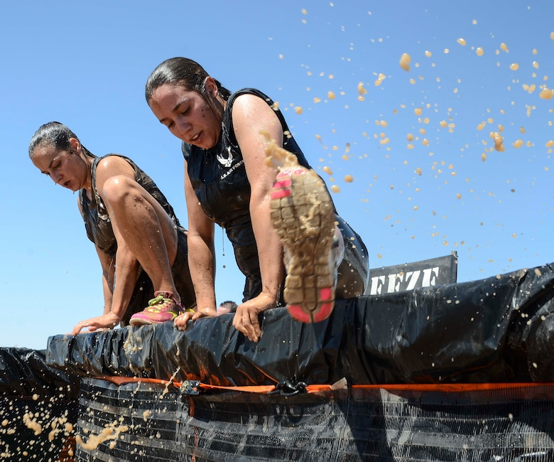 Members from 12th Air Force (Air Forces Southern) exit a tank filled with cold water during Hard Charge Televised Obstacle Mission at the Pima County Fairgrounds in Tucson, Ariz., on March 29 as a team. The team of 11 members completed the four mile course with of obstacles designed to utilize a mix of strength, stamina, balance, and body awareness that pushed participants to both mental and physical fatigue.  (U.S. Air Force photo by Staff Sgt. Adam Grant/Released)