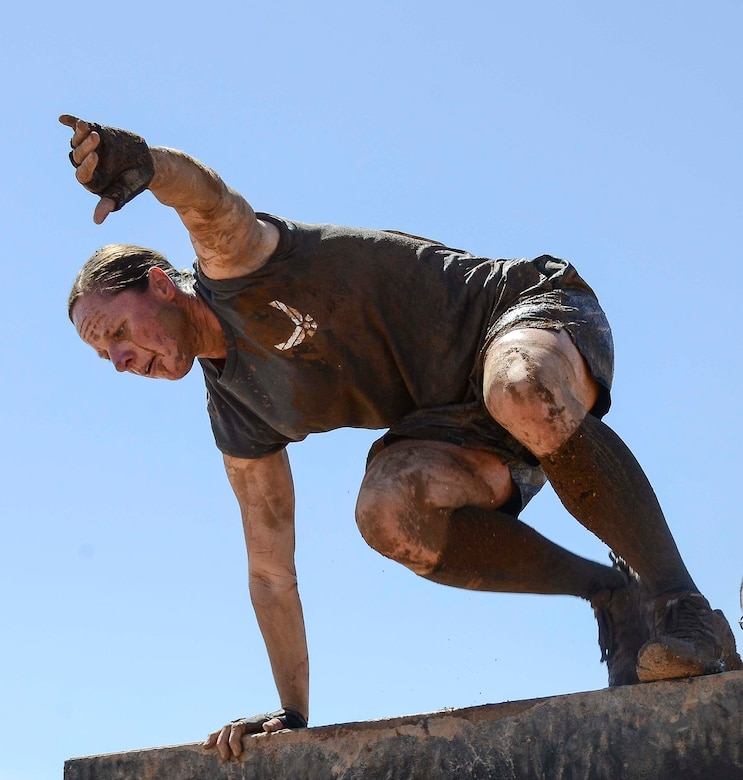 Capt. Yvonne Nollmann, 12th Air Force (Air Forces Southern) Section Commander, hurdles over a wall during the Hard Charge Televised Obstacle Mission at the Pima County Fairgrounds in Tucson, Ariz., on March 29. Climbing, crawling and sprinting were a few of the many ways the members form 12th AF maneuvered though the rigorous four-mile 37-obstacle course. (U.S. Air Force photo by Staff Sgt. Adam Grant/Released)