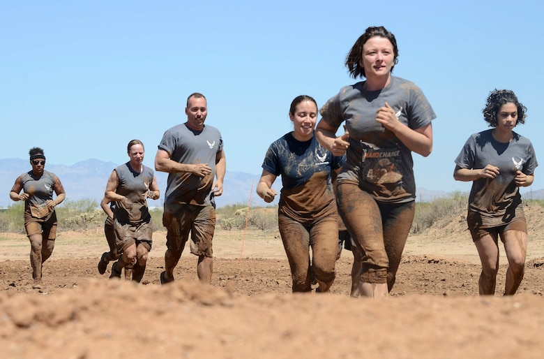 Members from 12th Air Force (Air Forces Southern) jog to their next obstacle during the Hard Charge Televised Obstacle Mission at the Pima County Fairgrounds in Tucson, Ariz., on March 29. The team of 11 members completed the four mile course with of obstacles designed to utilize a mix of strength, stamina, balance, and body awareness  that pushed participants to both mental and physical fatigue. (U.S. Air Force photo by Staff Sgt. Adam Grant/Released)