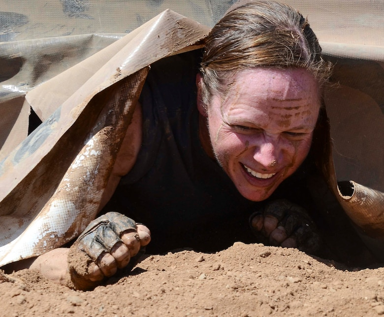 Capt. Yvonne Nollmann, 12th Air Force (Air Forces Southern) Section Commander, crawls from underneath a tarp during the Hard Charge Televised Obstacle Mission at the Pima County Fairgrounds in Tucson, Ariz., on March 29. Climbing, crawling and sprinting were a few of the many ways the members form 12th AF maneuvered though the rigorous four-mile 37-obstacle course. (U.S. Air Force photo by Staff Sgt. Adam Grant/Released)