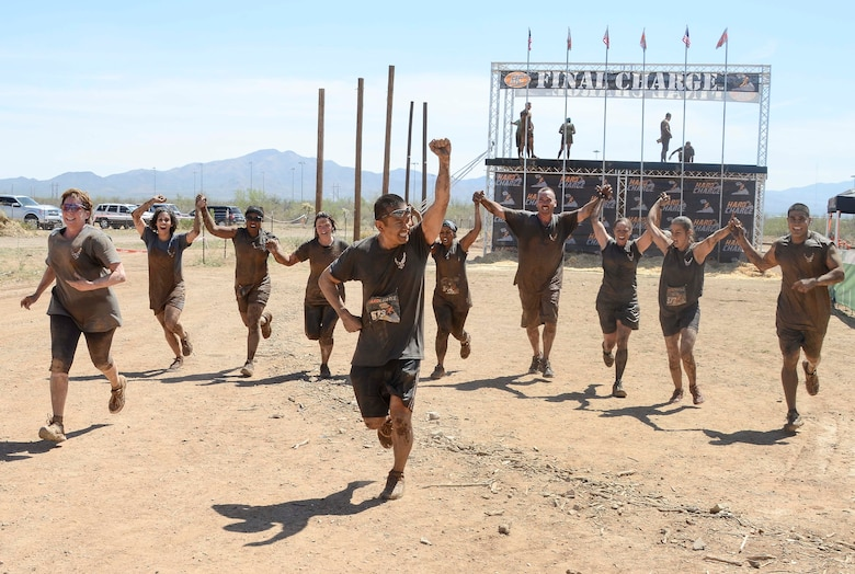 Members from 12th Air Force (Air Forces Southern) hold hands as the complete the Hard Charge Televised Obstacle Mission at the Pima County Fairgrounds in Tucson, Ariz., on March 29 as a team. The team of 11 members completed the four mile course with of obstacles designed to utilize a mix of strength, stamina, balance, and body awareness  that pushed participants to both mental and physical fatigue. (U.S. Air Force photo by Staff Sgt. Adam Grant/Released)