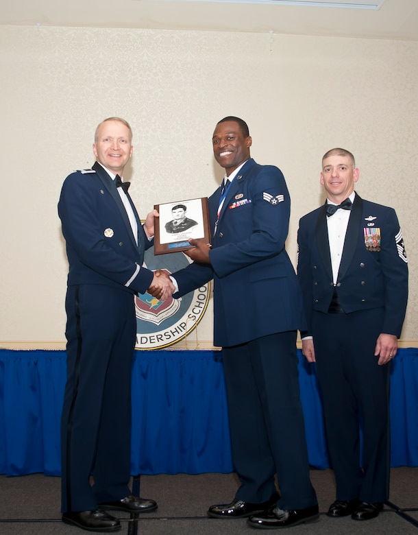 Col. Darren Hartford, 437th Airlift Wing commander, and Chief Master Sgt. Shawn Hughes, 437th AW command chief, present the John L. Levitow Award to Senior Airman Maurice Hargraves, 437th Aircraaft Maintenance Squadron crew chief, during the Airman Leadership School Class graduation March 28, 2014, at Joint Base Charleston - Air Base, S.C. The Levitow award is given for a student's exemplary demonstration of excellence, both as a leader and a scholar. (U.S. Air Force photo/ Staff Sgt. William A. O'Brien)