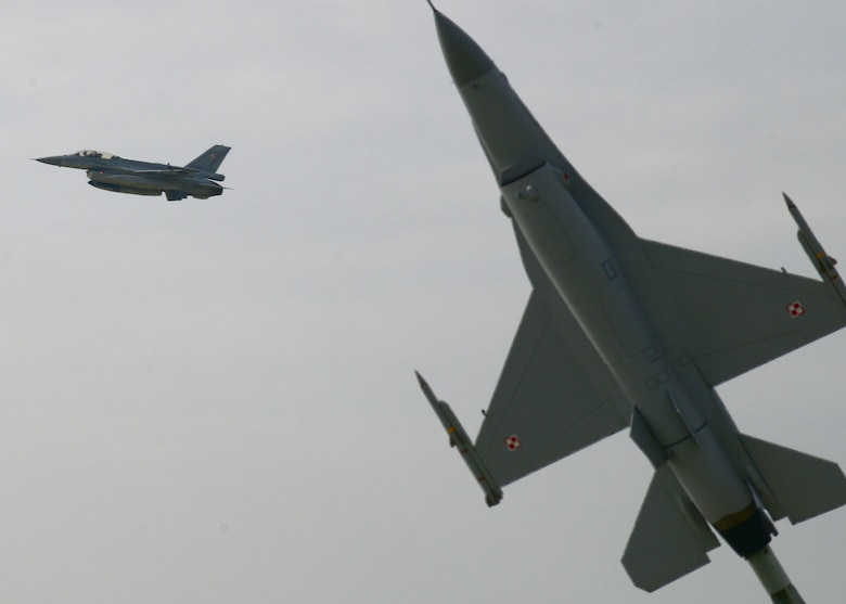 A Polish F-16 Fighting Falcon fighter aircraft passes a static display of an F-16 after takeoff, April 1, 2014, at Łask Air Base, Poland. The Polish armed forces and approximately 200 U.S. personnel have built partnership capacity together here since March 13, to increase cooperation and strengthen operational understanding of the other's military processes, strengthening interoperability with a key NATO ally. (U.S. Air Force photo/Airman 1st Class Ryan Conroy/Released)