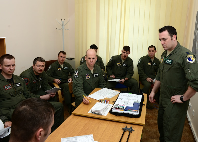 U.S. and Polish pilots listen to a pre-flight briefing, April 1, 2014, prior to their first training sortie together at Łask Air Base, Poland. Some of the training will focus on communication effectiveness and familiarization of techniques to strengthen interoperability with a key NATO ally since the 555th Fighter Squadron from Aviano Air Base, Italy, and the Polish air force's 10th Tactical Squadron from Łask employ the F-16 Fighting Falcon fighter aircraft. (U.S. Air Force photo/Airman 1st Class Ryan Conroy/Released)