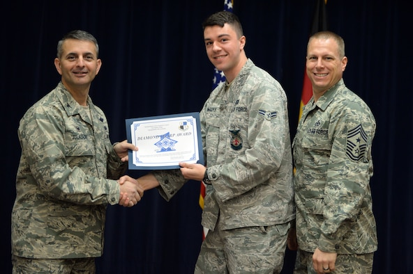 U.S. Air Force Airman 1st Class Scott Weeks, 52nd Civil Engineer Squadron firefighter from Green Bay, Wis., accepts a Diamond Sharp Award from U.S. Air Force Col. David Julazadeh, 52nd Fighter Wing commander, and U.S. Air Force Chief Master Sgt. Matt Grengs, 52nd FW command chief, right, during an awards ceremony at Club Eifel at Spangdahlem Air Base, Germany, March 31, 2014. Weeks and 16 fellow Spangdahlem Airmen received a certificate and coin as part of the First Sergeants Council's quarterly recognition program. (U.S. Air Force photo by Senior Airman Alexis Siekert)