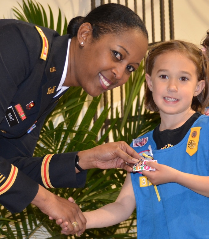 ALBUQUERQUE, N.M., -- District Commander Lt. Col. Gant rewards one of the Girl Scouts with her Owl Prowl badge, March 22, 2014.