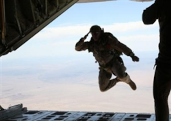 Marine Corps Master Sgt. Randy Messineo, operation chief, Company B, 1st Reconnaissance Battalion, and a native of Boston, salutes the crew of a C-130 Hercules aircraft as he jumps out of it during a double-bag static line course held in Parker, Ariz., March 24, 2014. A static line is a cord attached from one end of the aircraft to the other. When the Marine jumps from the plane, the line pulls the deployment bag out of the pack on the Marine's back causing the parachute to inflate.