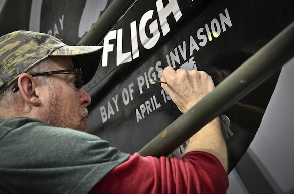 Students and directors from the University of Alabama-Birmingham paint nose art on a KC-135R aircraft. The design commemorates the 117th Air Refueling Wing's participation in the 1961 Bay of Pigs operation. Tech. Sgt. Aaron Sharit, a crew chief from the 117th Maintenance Group, created the design and was inspired by a combination of logos and graphics that were used on some of the aircraft during the invasion.  (U.S. Air National Guard photo by Master Sgt. Ken Johnson/Released)