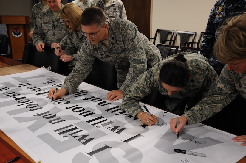 """Leadership from Joint Base Charleston sign a Sexual Assault Awareness Banner April 1, 2014, at Joint Base Charleston-Air Base. The banner reads """"I will not tolerate it, I will not condone it, I will not ignore it,"""" and will be put on display at a heavily-trafficked section of the base. (U.S. Air Force photo by 1st Lt. Christopher Love)"""