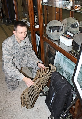 Lt. Col. Chris Lemanski kneels beside a low profile parachute and an aircrew survival vest and beneath a glass-encased helmet and aviator lenses all developed under the auspices of the Agile Combat Support division.