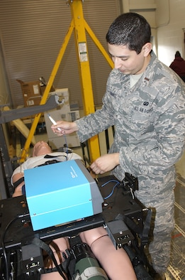 Second Lt. Carlos Suarez ll, a test engineer, demonstrates how an electrical surgical generator cauterizes wounds and blood vessels and allows for in-flight surgery.
