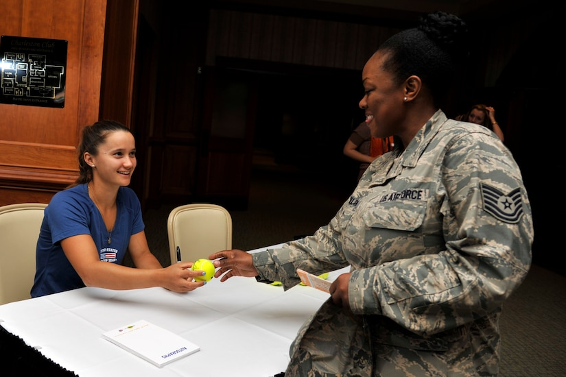 Professional tennis player Lauren Davis, gives an autographed tennis ball to Tech. Sgt. Crystal Collins, a career development professional with the 315th Force Support Squadron, during a morale tour of Joint Base Charleston, S.C. April 1, 2014. The tour included signing autographs at the Charleston Club followed by a C-17A Globemaster III static tour. (U.S. Air Force photo/Staff Sgt. Renae Pittman)