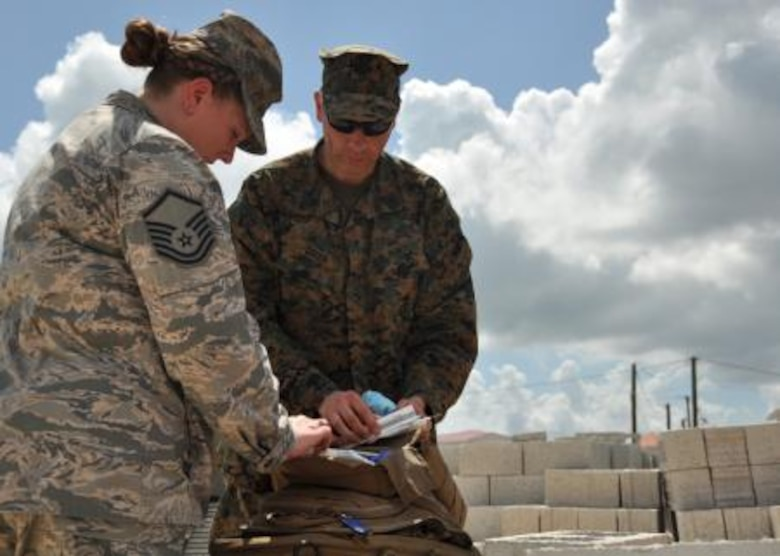 U.S. Air Force Master Sgt. Tara Harrison, independent duty medical technician and New Horizons lead medic for U.S. service members, discusses the availability of medical supplies with U.S Navy Petty Officer 1st Class Tim Greer, a 472nd Marine Wing Support Squadron hospital corpsman, March 31, 2014, at the Edward P. Yorke school construction site in Belize City, Belize. Greer, a six-year corpsman from Shelton, Conn., tasked with providing medical care to U.S. Marines, and Harrison, a 19-year IDMT, discussed supply inventories and medical considerations as they provide care for U.S. service members during New Horizons Belize 2014. (U.S. Air Force photo by Tech. Sgt. Kali L. Gradishar/Released)