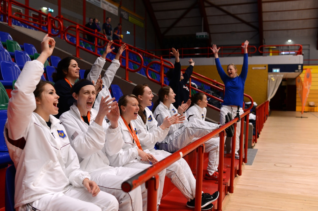 Members of the U.S. Air Forces in Europe and Air Forces Africa women's volleyball team cheer for the men's team during a Headquarters Allied Air Command Inter-Nation Sports Programme Volleyball Championship match in Amsterdam, March 27, 2014. The women's team has placed first in six of the last six championships they have participated in including this year's tournament. (U.S. Air Force photo by Senior Airman Gustavo Castillo/Released)