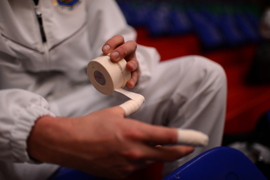 Stuart Sherman, U.S. Air Forces in Europe and Air Forces Africa men's volleyball team outside hitter from Tuscon, Ariz., tapes his fingers before a Headquarters Allied Air Command Inter-Nation Sports Programme Volleyball Championship match in Amsterdam, March 26, 2014. Players tape their fingers to stiffen their joints while blocking a ball to avoid injury. (U.S. Air Force photo by Senior Airman Gustavo Castillo/Released)