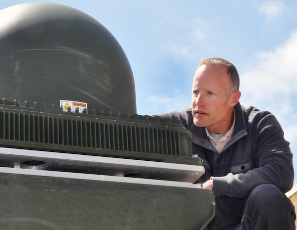 Marine Corps Tactical Systems Support Activity technical support officer and Marine Corps Tester of the Year Scot Hoesly surveys the Network-on-the-Move KU satellite communications antenna housing mounted aboard an Assault Amphibious Vehicle. Hoesly directs MCTSSA's testing of the NOTM/AAV platform that, when fielded, will provide a significantly new amphibious command-and-control capability to the Marine Corps.