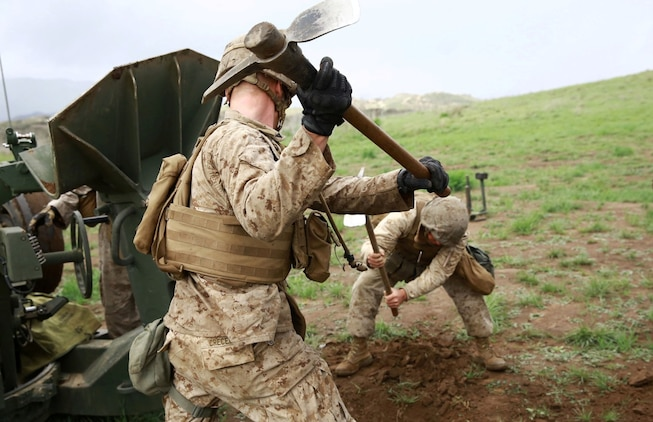 Marines with India Battery, 1st Battalion, 11th Marine Regiment, dig a trench to properly emplace the M777A2 Howitzer during a battalion fire exercise aboard Marine Corps Base Camp Pendleton, Calif., March 27, 2014. Once emplaced, the weapon system can accurately engage targets from 18 miles away. (U.S. Marine Corps photo by Lance Cpl. Jonathan Boynes/released)