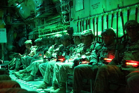 Marines with Bravo Company, 1st Reconnaissance Battalion, sit in a C-130 Hercules waiting for the command to parachute out of the plane during a double-bag static line course held in Parker, Ariz., March 24, 2014. A static line is a cord attached from one end of the aircraft to the other. When the Marine jumps from the plane, the line pulls the deployment bag out of the pack on the Marine's back causing the parachute to inflate. The 24 Marines taking the course were evaluated on their jump form, their formation in the air and their landing. They conducted both day and night jumps and were required to jump a total of 12 times before they passed the course. (Photo by Lance Cpl. Christopher J. Moore/Released)