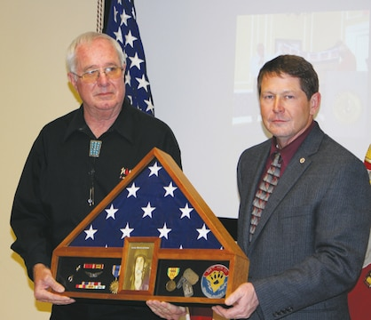 Jerry Laney (left) safety coordinator, C4, Marine Corps Logistics Command, receives a shadow box from Hal Gobin, director, C4, LOGCOM, at his retirement March 27 in LOGCOM's Multipurpose Room, Building 3700.