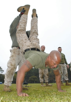 Gunnery Sgt. Quentin Green, packing specialist, Blount Island Command, Jacksonville, Fla., performs a buddy shoulder press while Maj. Miguel Toledano, company commander, Headquarters Company, BIC, holds his feet during the partner-series portion of the High Intensity Tactical Training level 1 training course, March 18-21. The training was held at Covella Pond aboard Marine Corps Logistics Base Albany.