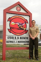 Sergeant Erica Bloomingdale, a native of Plymouth, Ohio, stands next to a sign displaying the unit logo for Marine Transport Squadron 1, March 28, 2014. Bloomingdale is a loadmaster for the VMR-1's C-9B Skytrain and the ground-training noncommissioned officer for the squadron.