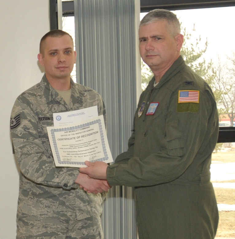 STRATTON AIR NATIONAL GUARD BASE, N.Y. -- Col. Shawn Clouthier (right), 109th Airlift Wing commander, presents Tech. Sgt. Robert Harrington with a certificate of recognition March 25, 2014, from Air Mobility Command for outstanding performance during the 109th AW's recent Unit Effectiveness Inspection. Harrington, of the 109th Communications Flight,was part of the Inspector General Communications Support Team, which received team recognition. Other members of the team not pictured were Master Sgt. Christopher Moore, Tech. Sgt. Jodi Habbinger, Tech. Sgt. Henry Smith, Senior Airman Matthew Almy, Airman 1st Class Collin Eustis, Airman 1st Class Joshua Speziale and Airman 1st Class Nicholas Tousignant. (Air National Guard photo by Master Sgt. William Gizara/Released)
