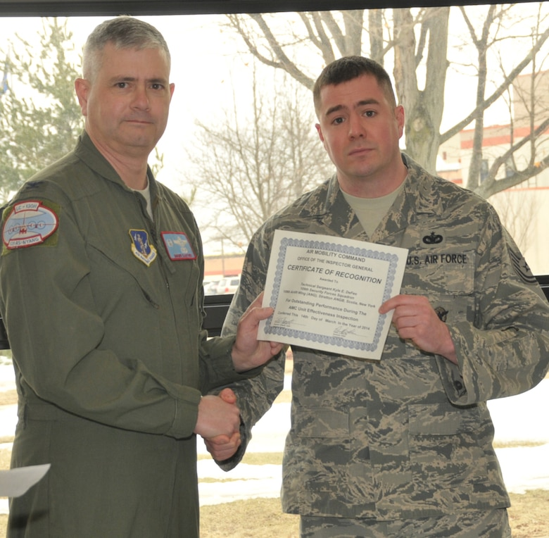 STRATTON AIR NATIONAL GUARD BASE -- Col. Shawn Clouthier (left), 109th Airlift Wing commander, presents Tech. Sgt. Kyle DeFeo with a certificate of recognition March 25, 2014, from Air Mobility Command for outstanding performance during the 109th AW's recent Unit Effectiveness Inspection. DeFeo is assigned to the 109th Security Forces Squadron. (Air National Guard photo by Master Sgt. William Gizara/Released)