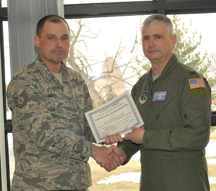 STRATTON AIR NATIONAL GUARD BASE -- Col. Shawn Clouthier (right), 109th Airlift Wing commander, presents Tech. Sgt. Jeremy Muller with a certificate of recognition March 25, 2014, from Air Mobility Command for outstanding performance during the 109th AW's recent Unit Effectiveness Inspection. Muller is assigned to the 109th Logistics Readiness Squadron. (Air National Guard photo by Master Sgt. William Gizara/Released)