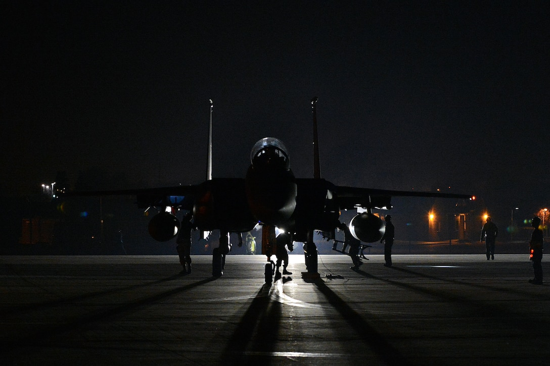Airmen perform early-morning checks on an F-15E Strike Eagle as the 492nd Fighter Squadron prepares to deploy from the flightline on Royal Air Force Lakenheath, England, April 1, 2014. The 492nd FS departed to support a six-month deployment to the U.S. Central Command area of responsibility. (U.S. Air Force photo by Airman 1st Class Trevor T. McBride)