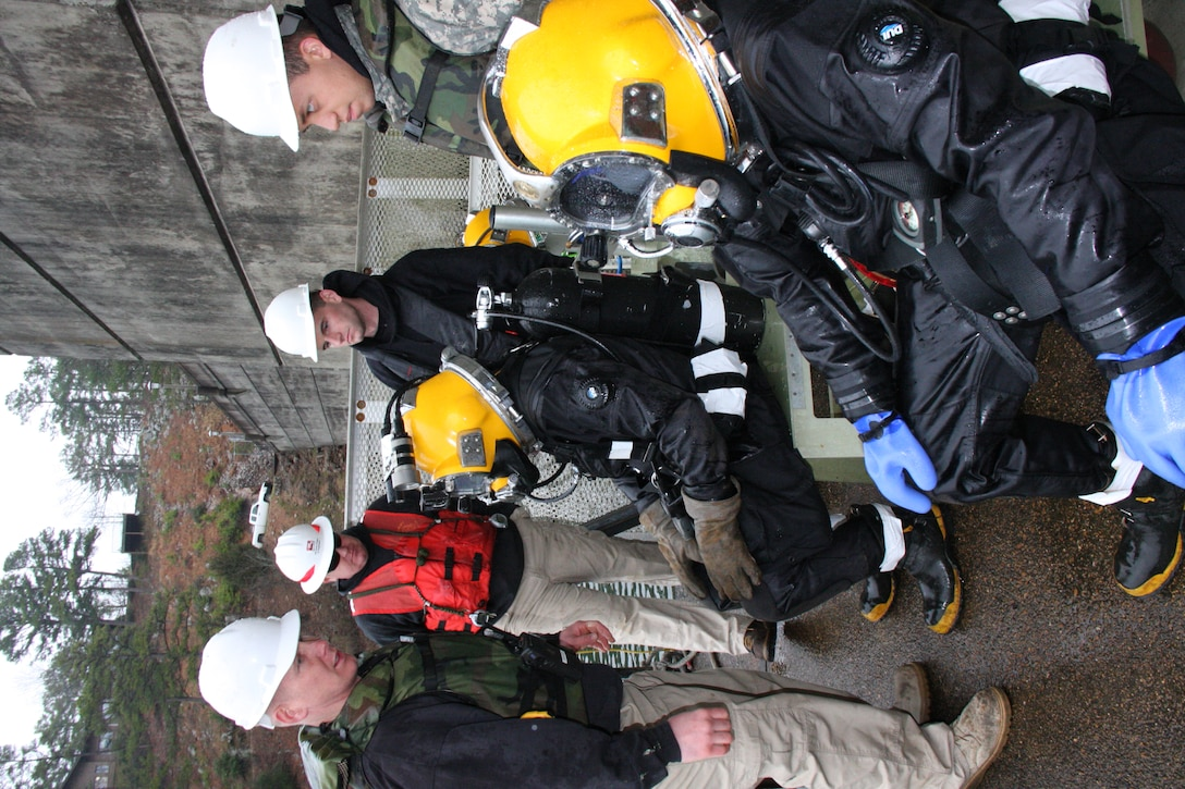 PHOTO: SGT Bryan Crowley, standing left, gives instructions to divers seated left to right, SGT Scott Wilson and PFC Kiley Bannan, while other dive team members look on, left to right, PFC Jesse Moore, SFC Blanchard Woodcox, and PFC Jordan Ramirez.