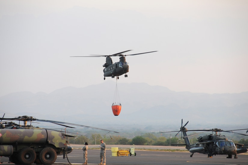 A U. S. Army CH-47 Chinook helicopter from the 1-228th Aviation Regiment takes off from Soto Cano Air Base, Honduras with a Bambi Bucket attached to fight a fire on a mountain ridge in Comayagua, Honduras.  The fire posed a threat to destroy homes and to cut off an access road to a local village.  Within one hour of receiving the call, the helicopters dumped about 6,180 gallons of water on the blaze to alleviate the danger.  (Photo by U. S. Air National Guard Capt. Steven Stubbs)