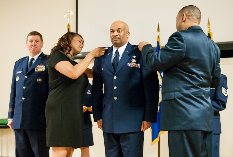 The wife and brother of Lt. Col. Charles Walker pin colonel's rank to his uniform during a promotion ceremony at the Kentucky Air National Guard Base in Louisville, Ky., March 22, 2014. Walker, staff judge advocate for Joint Forces Headquarters Air Component, Kentucky National Guard, is the first African-American to be promoted to the rank of colonel in Kentucky Air Guard history. (U.S. Air National Guard photos by Staff Sgt. Vicky Spesard)