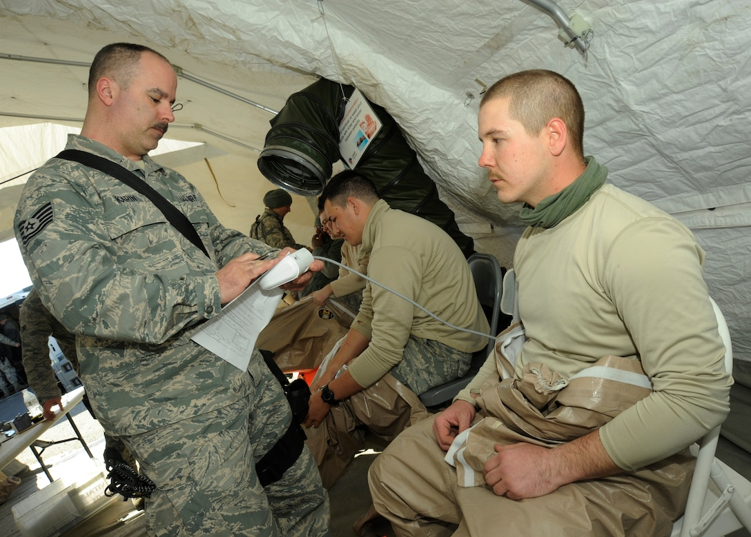 Air National Guard Tech. Sgt. Brad Kearin, a medic assigned to the 142nd Fighter Wing, takes vital readings from Army National Guard Pfc. Nichols Cherrick after his shift of work during the Vigilant Guard-Alaska 2014 exercise, near Joint Base Elmendorf-Richardson, Anchorage, Alaska, March 29, 2014. Both are members of the Oregon National Guard's CBRNE Enhanced Response Force Package (CERFP). (U.S. Air National Guard photo by Tech. Sgt. John Hughel, 142nd Fighter Wing Public Affairs/Released)