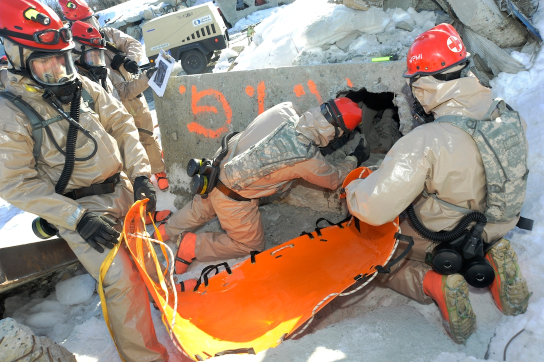 Members of the Oregon National Guard's CBRNE Enhanced Response Force Package (CERFP), use a drill hammer as they attempt to free a simulated victim during the Vigilant Guard-Alaska 2014 exercise, near Joint Base Elmendorf-Richardson, Anchorage, Alaska, March 29, 2014. (U.S. Air National Guard photo by Tech. Sgt. John Hughel, 142nd Fighter Wing Public Affairs/Released)