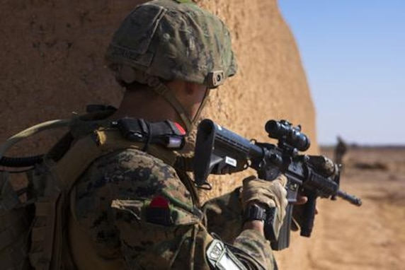 A U.S. Marine with Georgia Liaison Team 10, Regional Command (Southwest), peers around the corner of a desert compound during a patrol near Combat Outpost Eredvi, Helmand province, Afghanistan, Nov. 7, 2013. Marines joined forces with Georgian soldiers from the Batumi Light Infantry Battalion to conduct a patrol into an area known to have Taliban activity.