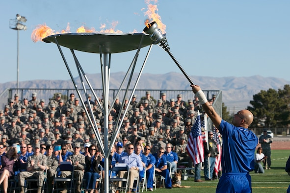 """Master Sgt. Christopher Aguilera lights the cauldron signifying the beginning of the Air Force Wounded Warrior Trails April 7, 2014, at Nellis Air Force Base, Nev. Aguilera, who is a survivor of the June 9, 2010 """"Pedro 66"""" helicopter crash in southwest Afghanistan, will participate in in seven events during the trials. (U.S. Air Force photo/Lorenz Crespo)"""