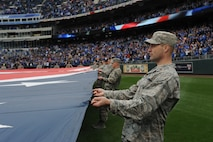Airmen from Whiteman Air Force Base, Mo., participate in a flag detail at Kauffman Stadium during the Kansas City Royals season opener April 4, 2014. More than 100 Airmen from the base participate in the event. The Royals defeated the Chicago White Sox 7-5.  (U.S. Air Force photo by Airman 1st Class Joel Pfiester/Released)