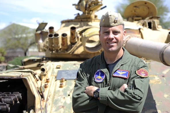 U.S. Navy Lieutenant Commander Eric Anderson, 354th Fighter Squadron assistant director of operations, poses in front of a tank, his unit's landmark at Davis-Monthan Air Force Base, Ariz., April 2, 2014. Anderson arrived at D-M in 2011 as part of an exchange program, giving him the opportunity to work under an Air Force command. (U.S. Air Force photo by Airman 1st Class Betty R. Chevalier/released)