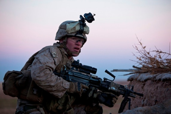 Lance Cpl. Nathan Chandler, a Logan, Ohio, native and machine gunner with 1st Battalion, 9th Marines, hunkers down behind a compound wall during a firefight with insurgents near the Bari Gul Bazaar, Nad Ali District, Helmand province, Afghanistan, Dec. 4. Nearly 100 Marines and coalition allies engaged in a prolonged firefight with insurgents while patrolling the area to interdict Taliban movements and weapons caches and gather intelligence around the bazaar. The interdiction force landed by helicopter during the cover of night and began sweeping through the area with the help of Afghan forces and interpreters before engaging Taliban fighters in a firefight that lasted nearly four hours.