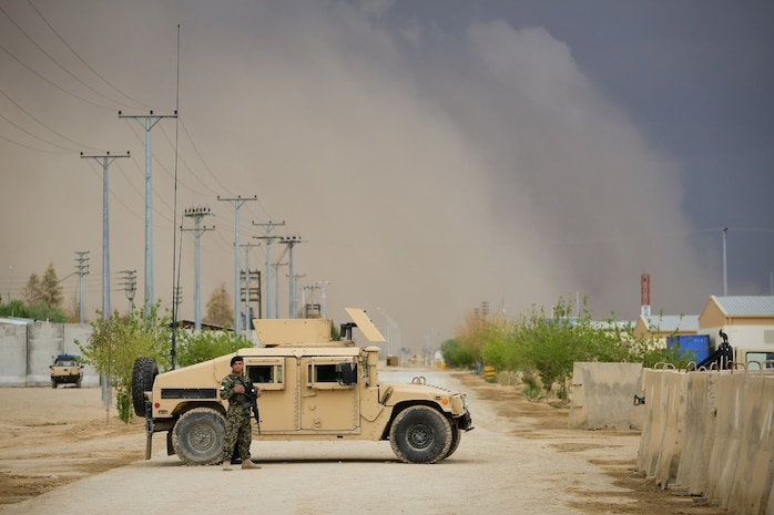 A Afghan National Army (ANA) soldier, assigned to the 215th Corps, stands next to an ANA Humvee while guarding the Operational Coordination Center- Regional (OCC-R) during the Afghan presidential elections, as a sandstorm approaches, aboard Camp Shorabak, Helmand province, Afghanistan, April 5, 2014. The 1393 (2014) presidential elections is the first year Afghan National Security Forces (ANSF) have taken the lead for such an event. (Official U.S. Marine Corps photo by Lance Cpl. Darien J. Bjorndal, Marine Expeditionary Brigade Afghanistan/ Not Released)