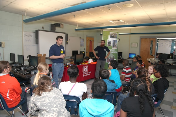 """FORT STEWART, Ga. – Mechanical Engineer Matt Kilmer (left) and Civil Engineer Craig Walters with the U.S. Army Corps of Engineers Savannah District, Fort Stewart Resident Office, talk to students at Diamond Elementary School about engineering careers with the Corps during a school-wide """"STEMposium"""" April 4, 2014. The event focused on getting children interested in Science, Technology, Engineering and Math (STEM) career fields."""