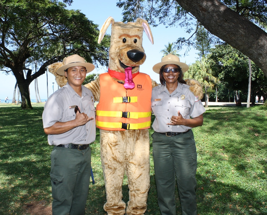 HONOLULU (April 5, 2014) - U.S. Army Corps of Engineers Park Rangers Don Espaniola and Angela Jones say Aloha to Bobber the Water Safety Dog after attending a beach and berm clean up as part of Earth Month 2014 at the Corps' Pacific Regional Visitor Center at Fort DeRussy.