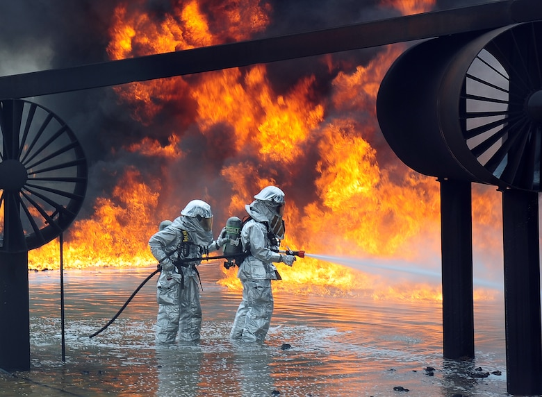 U.S. Air Force firefighters from the 7th Civil Engineer Squadron spray water onto a fire during a live fire training exercise April 2, 2014, at Dyess Air Force Base, Texas. In addition to wearing their fire proximity suits, firefighters must also wear self-contained breathing apparatus' that provide a source of clean oxygen, enabling them to work in the presence of smoke or other super-heated gases.  (U.S. Air Force photo by Senior Airman Kia Atkins/Released)