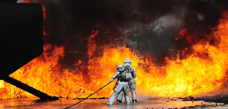 U.S. Air Force firefighters from the 7th Civil Engineer Squadron participate in live fire training exercise April 2, 2014, at Dyess Air Force Base, Texas. Teams from the Dyess Fire Department and Abilene Regional Airport Fire Department demonstrated various hose and firefighting procedures while engaging the controlled blaze. (U.S. Air Force photo by Senior Airman Kia Atkins/Released)