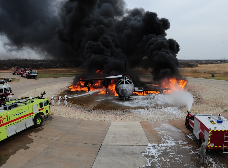 Firefighters from the 7th Civil Engineer Squadron and the Abilene Regional Airport Fire Department extinguish flames during a live fire training exercise April 2, 2014, at Dyess Air Force Base, Texas. The silver fire proximity suits that firefighters wear are manufactured from vacuum-deposited aluminized materials that designed to reflect high radiant heat produced by fire. (U.S. Air Force photo by Senior Airman Kia Atkins/Released)