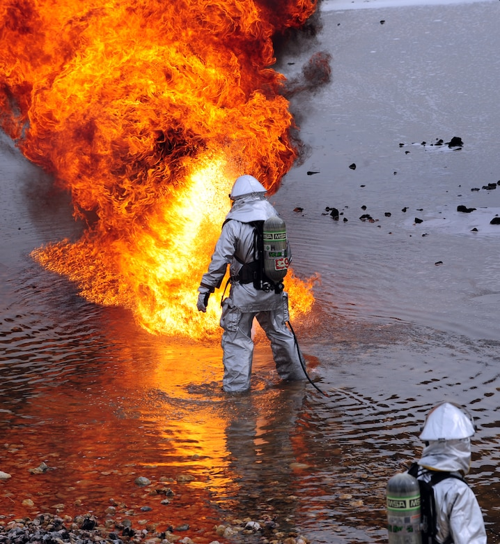 A U.S. Air Force firefighter from the 7th Civil Engineer Squadron ignites jet fuel during live fire training exercise April 2, 2014, at Dyess Air Force Base, Texas. The silver suits that firefighters wear are called fire proximity suits, which are designed to protect them from fire and extreme heat, like the heat encountered during aircraft fires. (U.S. Air Force photo by Senior Airman Kia Atkins/Released)