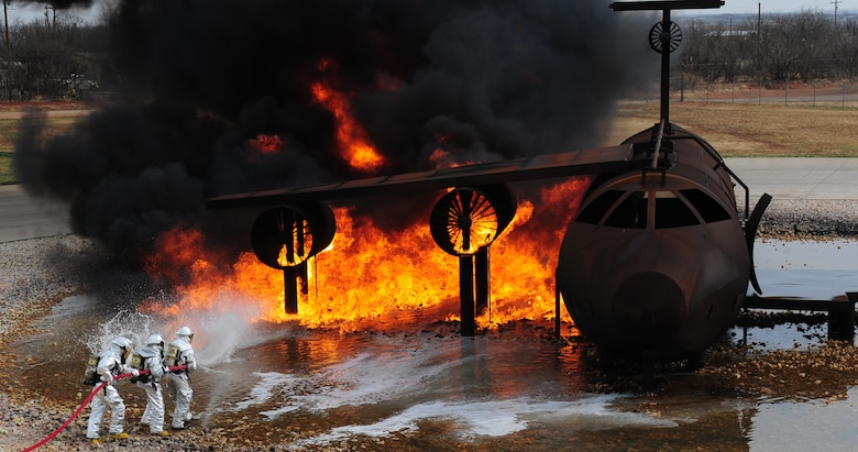 Firefighters from the Abilene Regional Airport Fire Department extinguish a fire during live fire training exercise April 2, 2014, at Dyess Air Force Base, Texas. Upon ignition, jet fuel starts to burn at 410 degrees Fahrenheit and can reach temperatures over 1,800 degrees. (U.S. Air Force photo by Senior Airman Kia Atkins/Released)