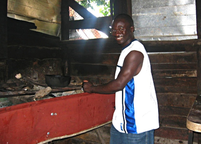 U.S. Air Force Master Sgt. Kenry Peart, 633rd Communications Squadron knowledge operations section chief, cooks on the wood-burning stove in the Parish of Manchester, Jamaica in this undated photo. Growing up, Peart worked with his family cooking meals, farming the fields and raising livestock. (Courtesy photo)