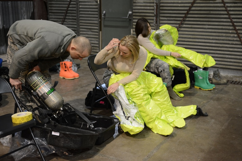 Tech. Sgt. Brian Black, 148th emergency management, helps the first team inspect and prepare their personal protective equipment during a field training exercise at Volk Field Air National Guard Base, Wis., April 4, 2014. Twenty-eight Airmen teamed up from six units for training that encompassed all hazard responses including radiation, chemical and biological situations. The training was part of emergency management's annual training requirement. (Air National Guard photo by Senior Airman Andrea F. Liechti)